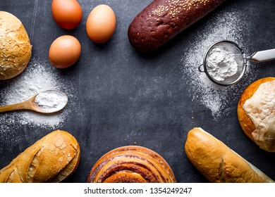 Ingredients for baking bakery products. Fresh bread, baguette, buns on a black chalkboard background. Copy space for recipe and text. Top view