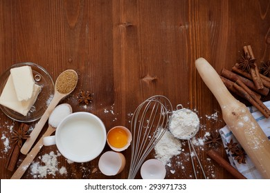 Ingredients for baking dough including flour, eggs, milk, butter, sugar, cinnamon, anise star, whisk and rolling pin on wooden rustic background, empty space for text, top view, toning