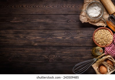 Ingredients for baking including eggs, oils, grains and flour, with sieve and whisk flour on empty wooden background with place for your text or recipes.