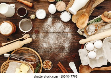 Ingredients for baking and kitchen utensils. Flour, eggs, sugar on wooden background