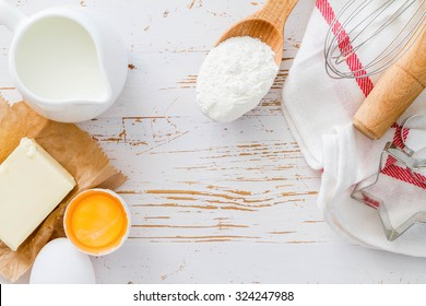 Ingredients for baking - milk butter eggs flour wheat, white wood background, copy space, top view