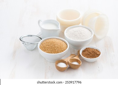 Ingredients for baking muffins on white wooden table, close-up