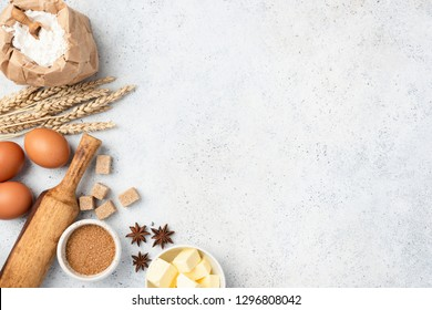 Ingredients for baking on background. Eggs, wheat flour, cubed butter, star anise, brown sugar cubes and rolling pin on concrete background with copy space