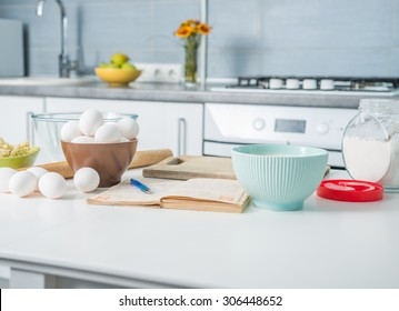 ingredients for baking and recioe book on a kitchen table