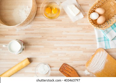 Ingredients for bread baking on light wooden background  with copyspace. Cutting board, eggs, salt, flour, raw eggs, milk, rolling pin, butter, towel, sieve.
