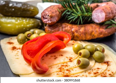 Ingredients of breakfast with cheese slices, sausage and vegetables.