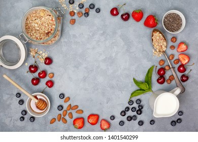 ingredients for breakfast: granola, chia seeds, fresh berries and nuts on a gray background. view from above.