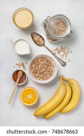 Ingredients for breakfast: muesli, milk, honey, orange, orange juice, bananas on a white concrete background. view from above