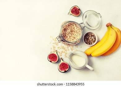 Ingredients for breakfast: oatmeal, milk, figs, bananas, pumpkin seeds. view from above. toning