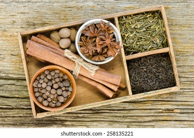 The ingredients for Chai tea in an antique cigar box with tea and spices on a rustic weathered barn board background