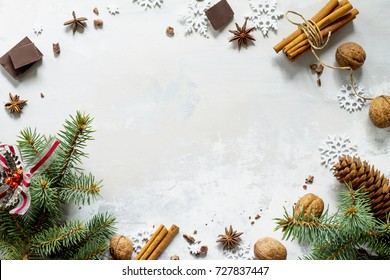 Ingredients for Christmas baking - chocolate, cinnamon, anise and nuts on a stone or slate background. Seasonal, food background.