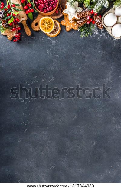 Ingredients for Christmas cooking, winter baking cookies, gingerbread, fruitcake, seasonal drinks. Cranberries, dried oranges, cinnamon, spices, flour on dark stone table, copy space top view