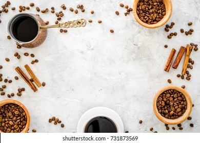 Ingredients for coffee. Roasted coffee beans and cinnamon on grey background top view copyspace