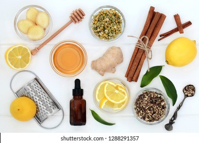 Ingredients for cold and flu remedy with ginger and cinnamon spice, eucalyptus aromatherapy oil, lemon fruit with honey on white wood background.