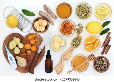 Ingredients for cold and flu remedy with thermometer, ginger, turmeric, echinacea, chamomile, cinnamon, eucalyptus oil, honey, vitamin tablets and capsules with orange and lemon fruit on white wood.