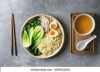 Ingredients for cooking asian dish udon noodles with boiled egg, mushrooms, boc choy, broth served in ceramic bowl with spoon and chopsticks over grey texture background. Top view, space.