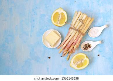 Ingredients for cooking asparagus on a light blue concrete background: fresh white asparagus, lemon, butter, salt, pepper. Top view, copy space.