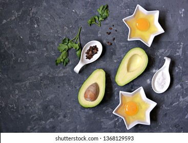 Ingredients for cooking baked avocado with egg on a dark concrete background: ripe avocado, cut in half, eggs, salt, pepper, parsley. Top view, copy space.