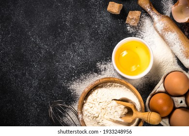 Ingredients for cooking baking, baking background. Flour, sugar, eggs, spices and utensil on black background. Top view with copy space.