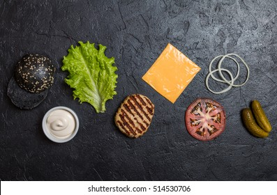 Ingredients for cooking black burger. Grilled chicken patty, buns, onion, tomatoes, lettuce, pickles, sauce, cheese over black background top view