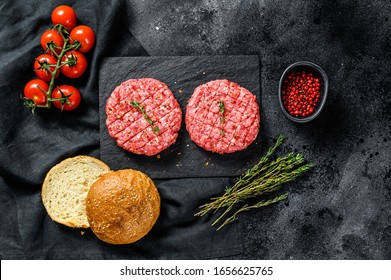 Ingredients for cooking burgers. Minced beef patties, buns, tomatoes, herbs and spices. Black background. Top view