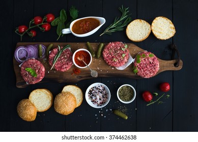 Ingredients for cooking burgers. Raw ground beef meat cutlets on wooden chopping board, red onion, cherry tomatoes, greens, pickles, tomato sauce, cheese, herbs, spices over black background, top view