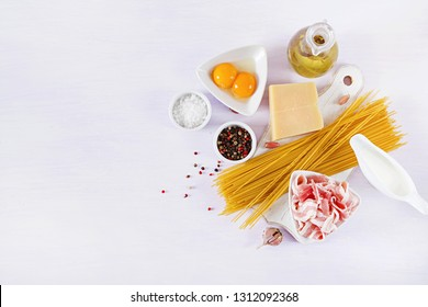 Ingredients for cooking Carbonara pasta, spaghetti with pancetta, egg, peppers, salt and hard parmesan cheese. Italian cuisine. Pasta alla carbonara. Top view, flat lay, copy space