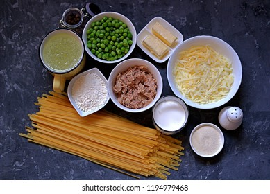 Ingredients for cooking casseroles of egg noodles with tuna and green peas on a dark gray background. Top view.