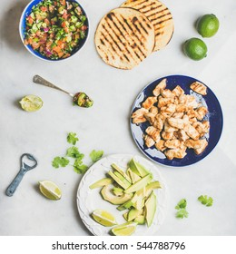 Ingredients for cooking chicken and avocado tacos. Fresh salsa, limes, grilled corn tortillas, grilled chicken fillet and avocado over grey marble table background, top view, square crop