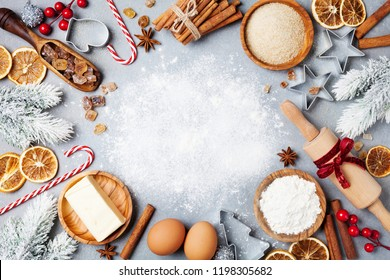 Ingredients for cooking christmas baking decorated with fir tree. Flour, brown sugar, eggs and spices top view. Bakery background.