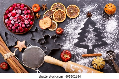 Ingredients for cooking Christmas baking: fir tree made from flour on a dark table,  frozen cranberry and dried fruits on dark background, top view