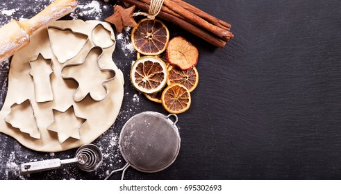 Ingredients for cooking Christmas gingerbread cookies : Gingerbread dough, baking shapes and kitchen utensils on dark table, top view
