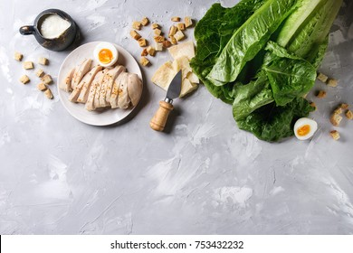 Ingredients for cooking classic Caesar salad. Sliced baked chicken breast, green roman salad, parmesan cheese, boiled egg, croutons, salt, jug of sauce over gray texture background. Top view, space.