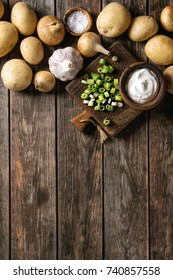 Ingredients for cooking dinner. Raw whole washed organic potatoes, onion, garlic, salt, spring onion and cream-fresh on cutting board over old wooden plank background. Top view with space