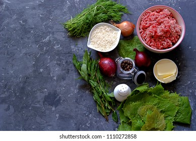 Ingredients for cooking dolma / sarma on a dark gray background. Minced meat, fresh grape leaves, butter, rice, mint, onion, dill, spices.