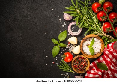Ingredients for cooking. Food background with spices, herbs and vegetables at black stone table. Top view with copy space.