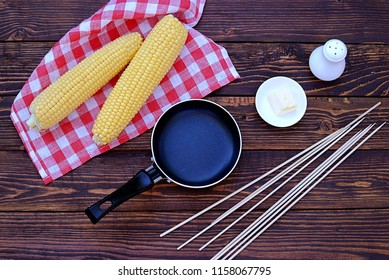 Ingredients for cooking fried cobs of corn. Corns of fresh sweet corn, butter, wooden skewers, spices, frying pan. Top view.