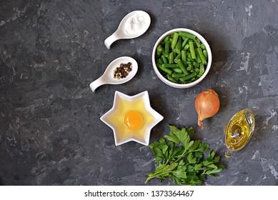 Ingredients for cooking green asparagus beans with scramble egg: raw green asparagus beans, egg, onion, salt, pepper, parsley, oil. Georgian cuisine. Top view, copy space.