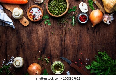 Ingredients for cooking green lentils with mushrooms and vegetables, spices and herbs, vintage wooden kitchen table background, place for text. Vegan or vegetarian food, clean food concept. T