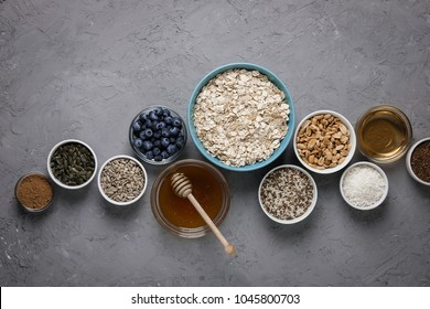 Ingredients for cooking homemade granola: oatmeal, raisins, coconut chips, honey, peanuts, cocoa, blueberries, vegetable oil, flax, sesame pumpkin and sunflower seeds Concrete background Top view