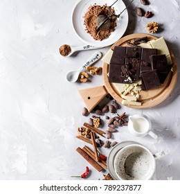 Ingredients for cooking hot chocolate. White and dark chopping chocolate on board, cocoa powder, cocoa beans, cream, cinnamon, sugar in spoons. Over gray texture background. Top view. Square image