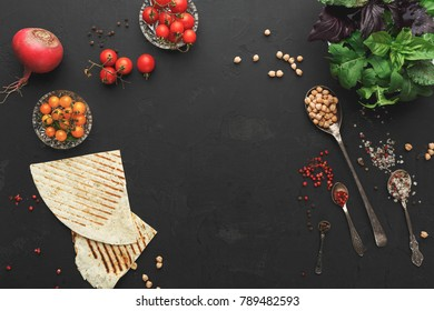 Ingredients for cooking hummus. Chickpeas, vegetables, greens and spices, fresh pitas black table background, top view, copy space