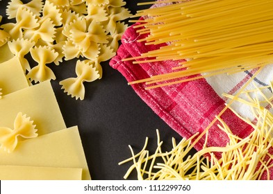 Ingredients for cooking, Italian food, scattered uncooked pasta farfalle, bowknot shaped pasta, lasagna, sheets of pasta, spaghetti and thin filini, on red kitchen towel, on black background