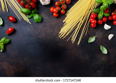 Ingredients for cooking italian pasta: spaghetti, tomato, basil and garlic on the black table. Top view image with a copy space