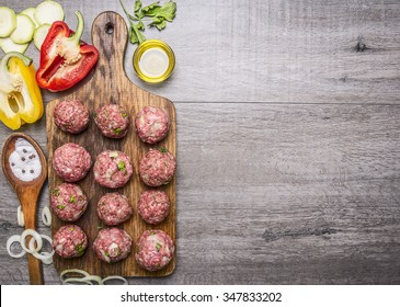 Ingredients for cooking meat balls with herbs and onions on a cutting board with tomatoes, peppers, zucchini and herbs on wooden rustic background top view border ,place for text
