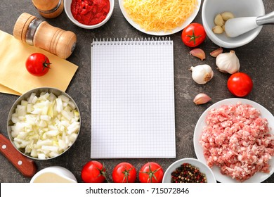 Ingredients for cooking meat lasagna with blank notebook on table, top view