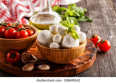 Ingredients for cooking - mozzarella cheese, tomatoes, basil, garlic, olive oil on the old wooden background.