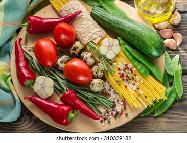 Ingredients for cooking pasta with vegetables - spaghetti, zucchini, tomatoes, garlic, rosemary, pepper. Selective focus