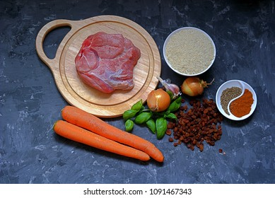 Ingredients for cooking pilaf on a dark gray concrete background. Meat on a wooden cutting board, carrots, rice, raisins, onion,  garlic, spices.