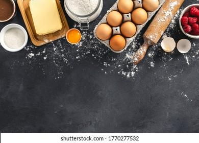 Zutaten zum Kochen von Himbeeren und Schokoladenkuchen auf dunklem Hintergrund mit Kopienraum Bäckerei-Hintergrund Draufsicht